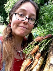 photograph of the author holding recently harvested carrots