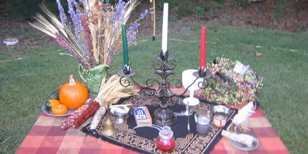 an altar on a table consisting of three candles and some other paraphrenalia