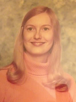 an older photo, yellowing with age, of Heron's mother, a blonde, caucasian woman