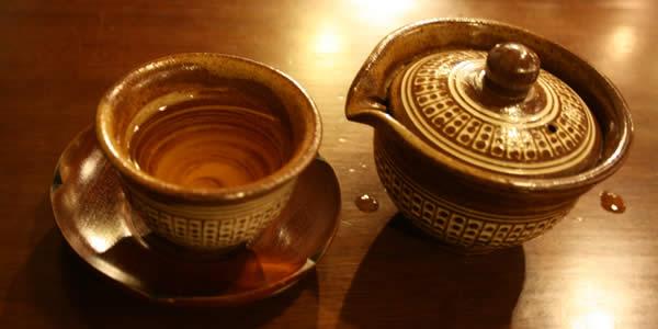a teapot, an empty tea cup, and a saucer