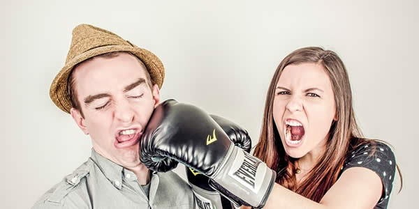 a woman wearing boxing gloves comically punching a man in the face