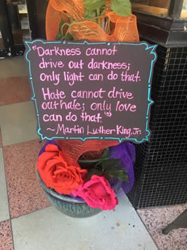 "a sign reading ""Darkness cannot drive out darkness; only light can do that. Hate cannot drive out hate; only love can do that"" by Dr. Martin Luther King, Jr."