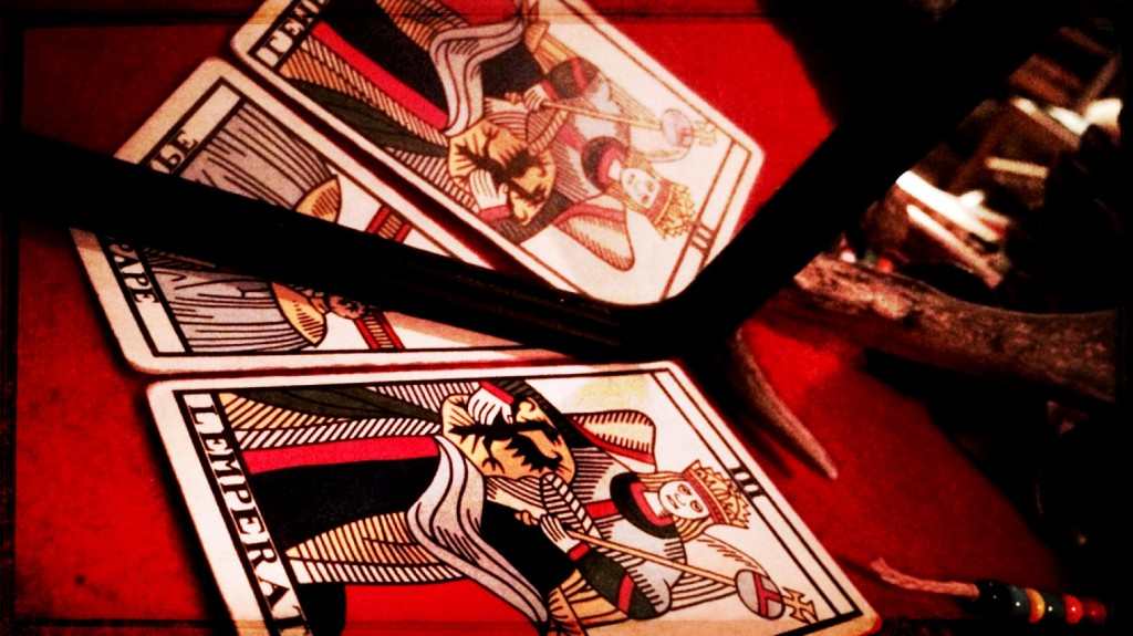 three tarot cards on a red table cloth