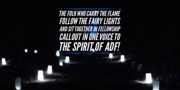 "Lit candles in a field with the text ""The folk who carry the flame, follow the fairy lights, and sit together in fellowship call out in one voice to the spirit of ADF!"""