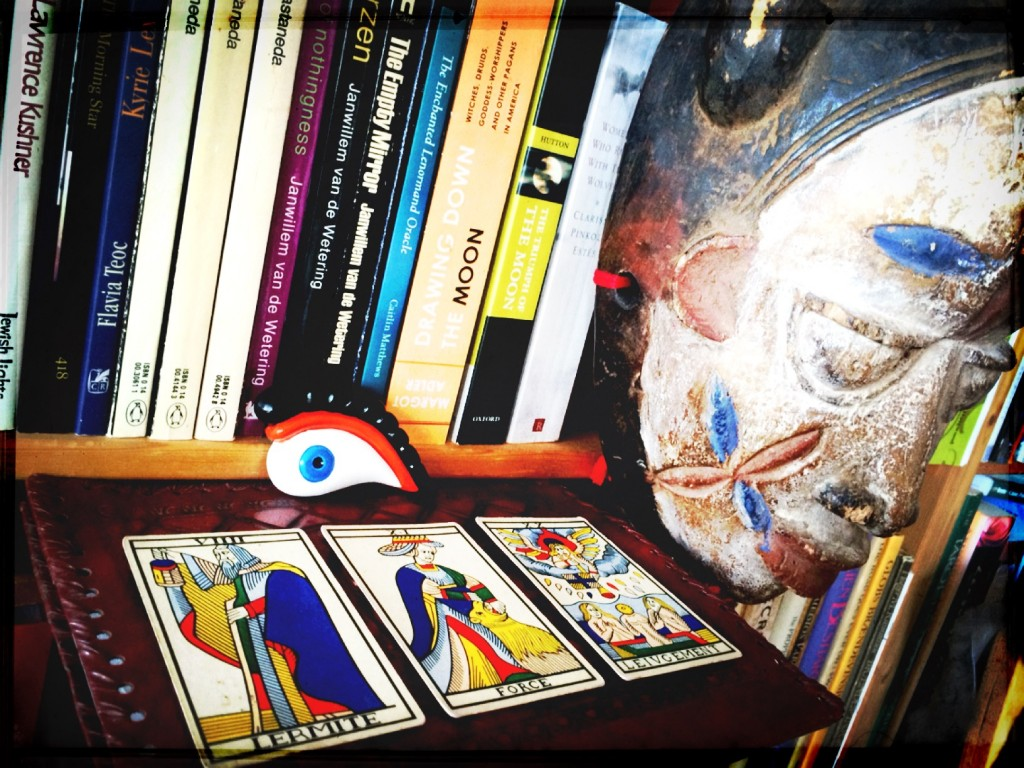 three tarot cards from the marseille tarot deck placed flat on a bookshelf