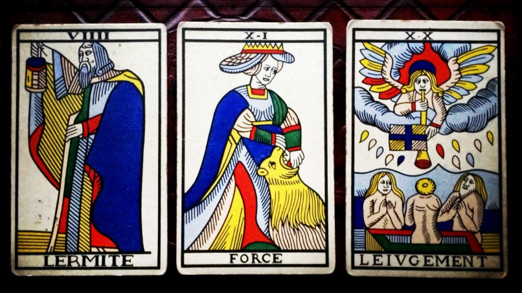 close up of three cards of the marseille tatot:  the hermit, strength, and judgement.