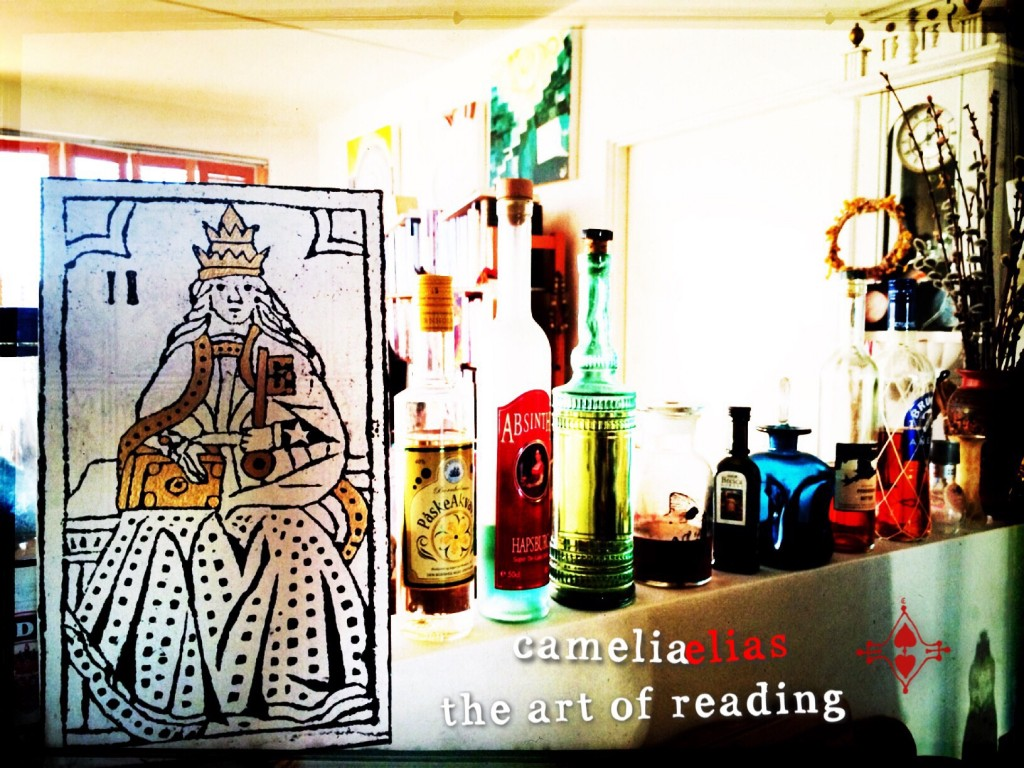 "a tarot card in the foreground with a living room in the background; the image includes the phrase""camelia elias, the art of reading"""