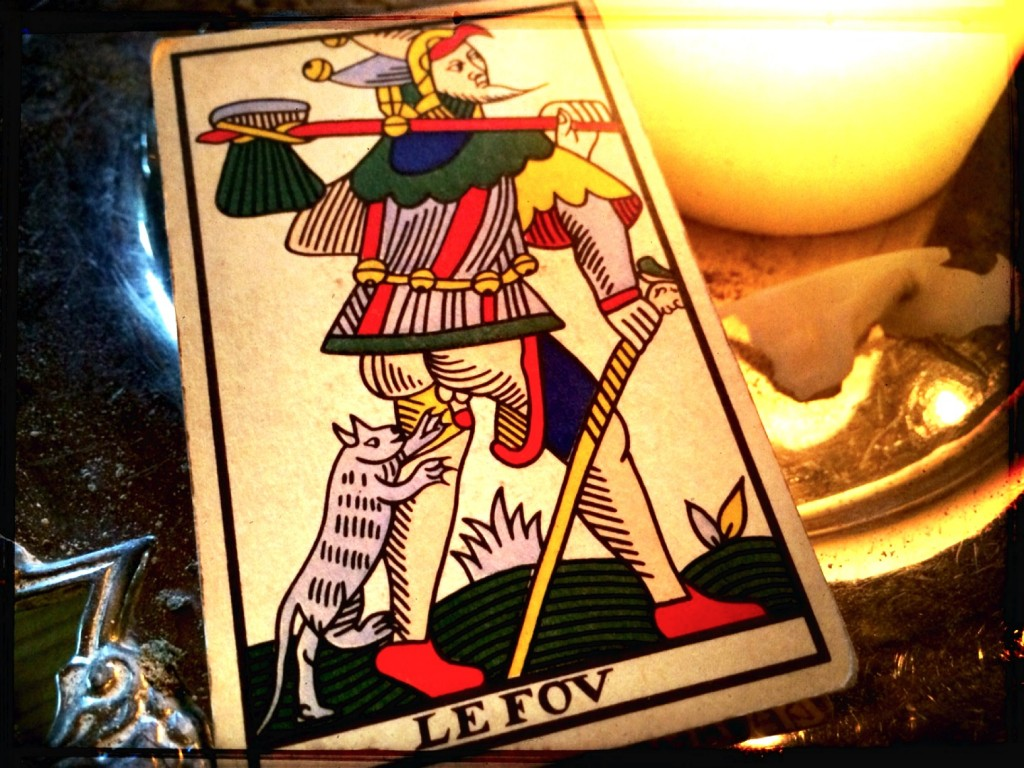 a tarot card, the fool, next to a lit candle on a table