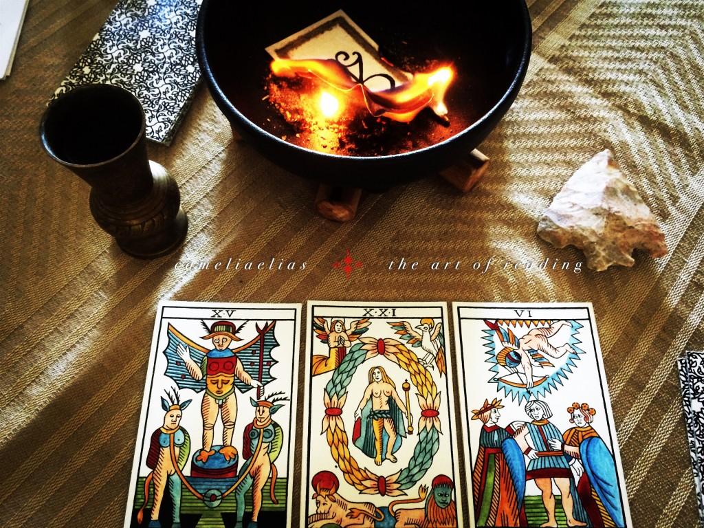 a photograph of three tarot cards placed near a calduron in which a fire burns