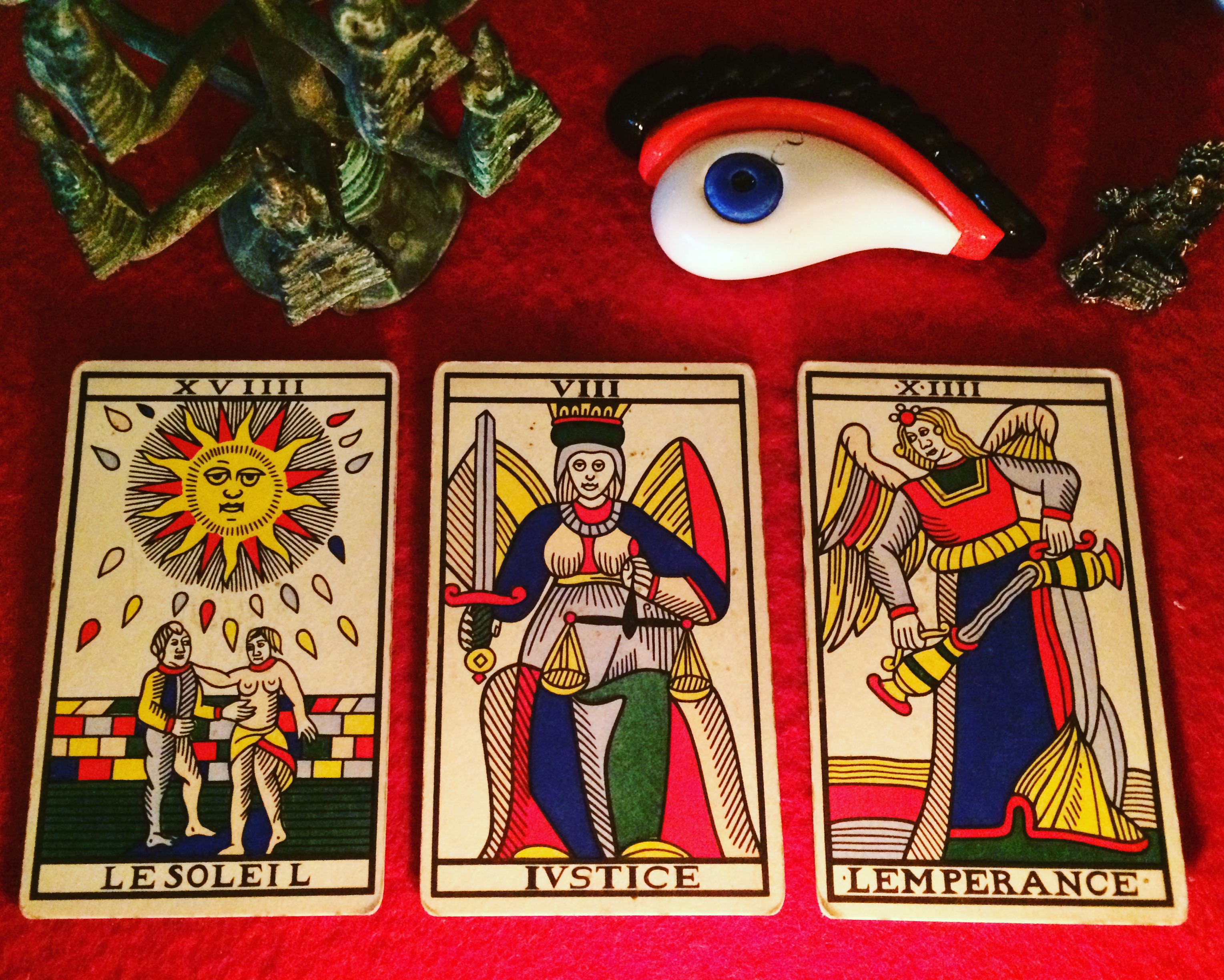 three tarot cards laid out on a red cloth:  the sun, justice, and temperance
