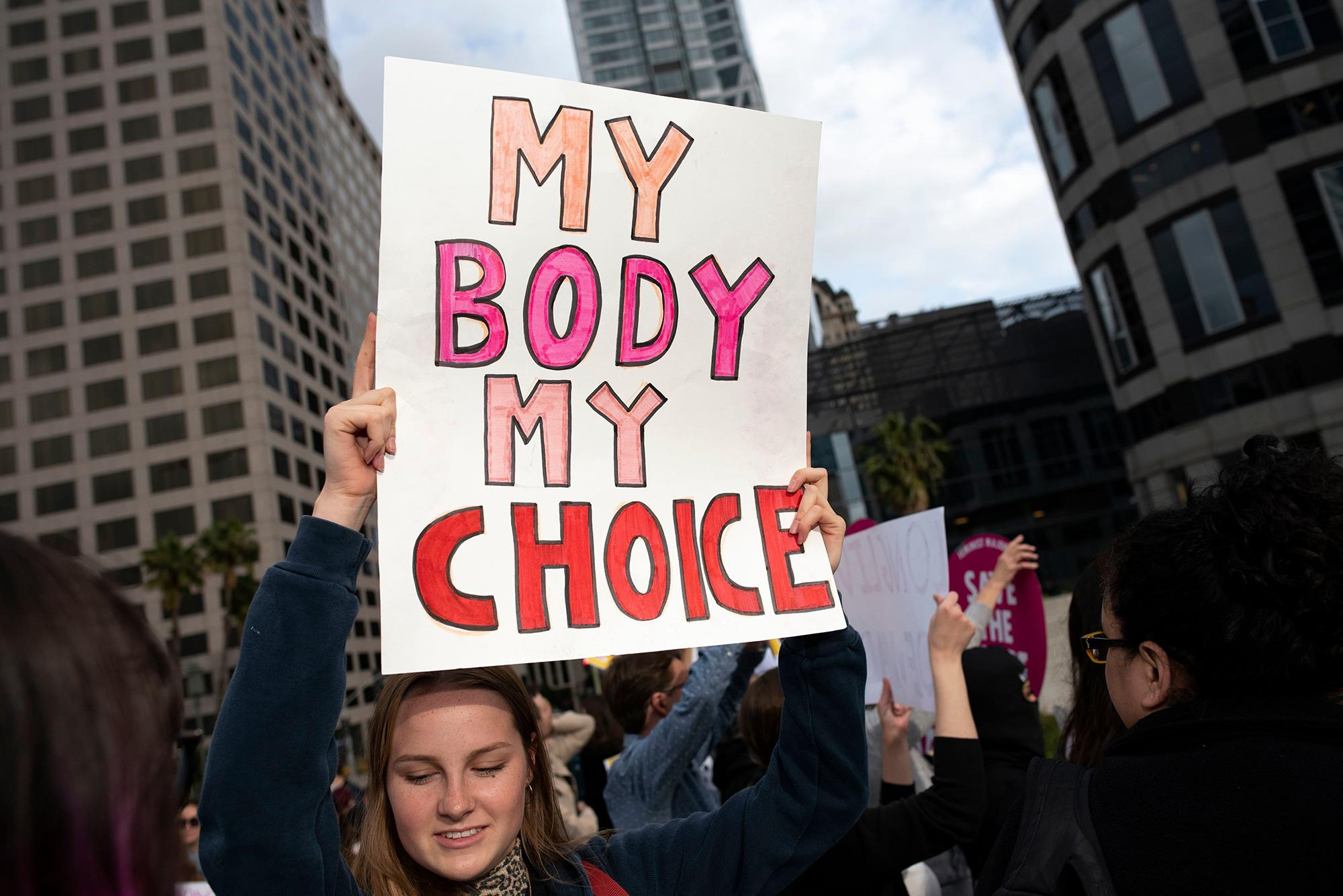 """A woman holding a sign that reads, """"My body my choice."""""""