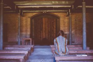 Girl sitting inside wooden church.
