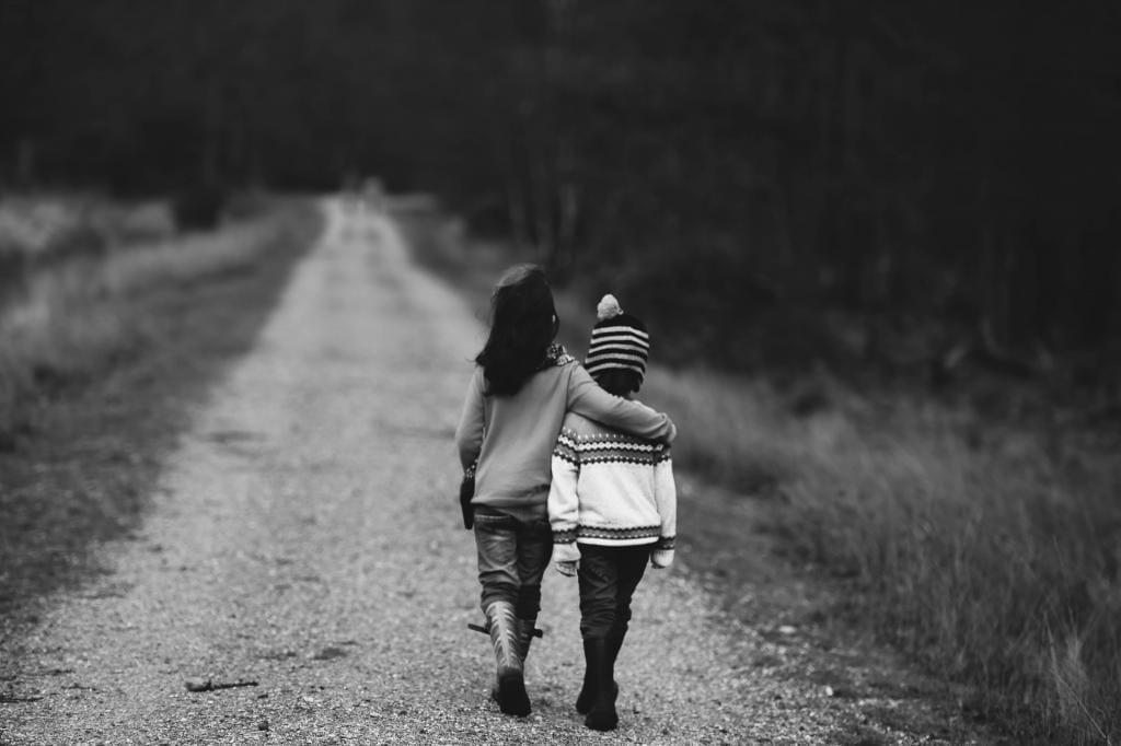 Kids walking down dirt road.