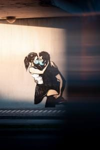 Wall graffiti of man and woman kissing with surgical mask on their face.