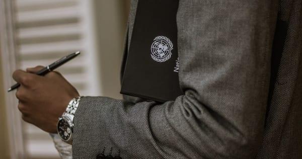 Ilyass Seddoug, Unsplash.com, CC0 Licensing - Black man in suit holding United Nations document