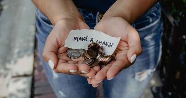 """Kat Yukawa, Unsplash.com, CC0 Licensing -- Photo of a woman's hands holding coins and a sign that reads: """"make a change"""""""