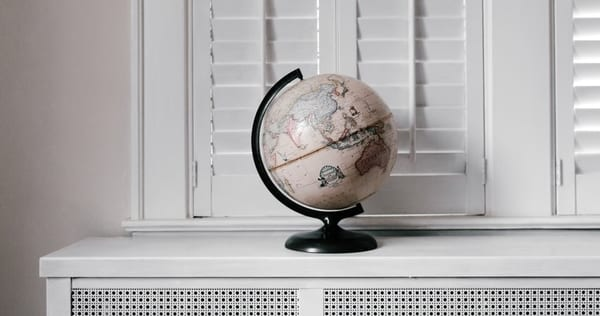 Image of a beige globe set on a white shelf, against a beige and white interior. Andrew Neel, Unsplash.com, CC0 Licensing