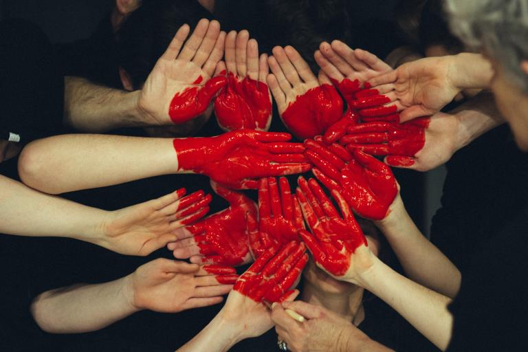 Image of many hands together, forming a painted heart. Tim Marshall, Unsplash.com, CC0 Licensing
