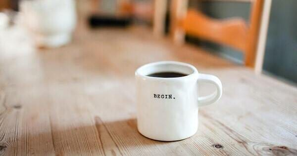 "White mug full of coffee, with the text ""begin"" on one side, on a wooden table that fades into a softened background with chairs. Danielle MacInnes, Unsplash.com, CC0 Licensing"