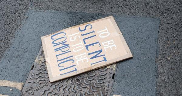 """Protest sign on the pavement, reading """"To be silent is to be complicit"""" - Photo by Ehimetalor Akhere Unuabona, Unsplash.com, CC0 Licensing"""