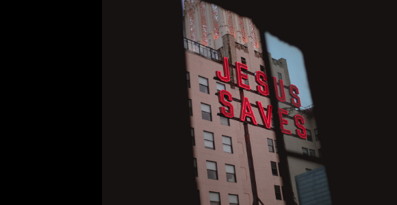 Neon lettering through a window spelling Jesus Saves.