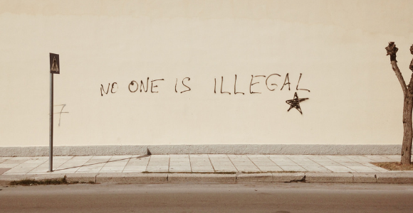 """Wall with writing that states, """"No one is illegal."""""""