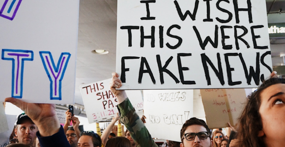 "Picture of a man holding sign stating ""I wish this were fake news."""