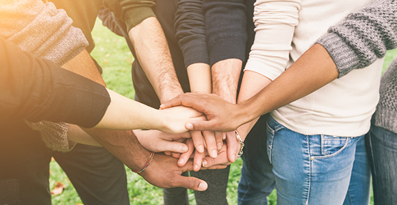 Picture of hands joined in community as a team