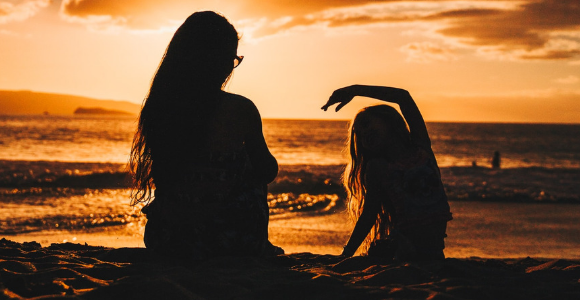 silhouette photo of woman and girl on shoreline to illustrate mothers and margins