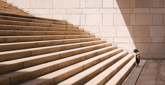 toddler's standing in front of beige concrete stair
