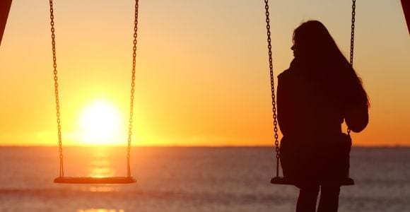 woman sitting alone on swing set
