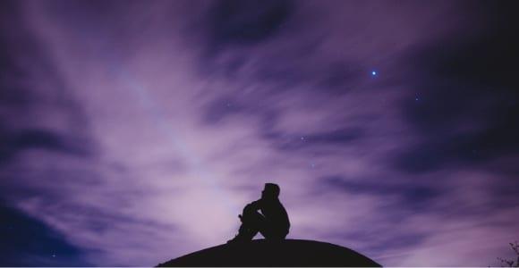 man sitting alone on hill