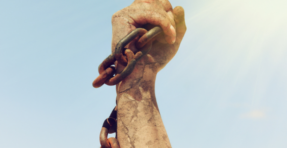 upraised fist with broken chain to illustrate no more slaves