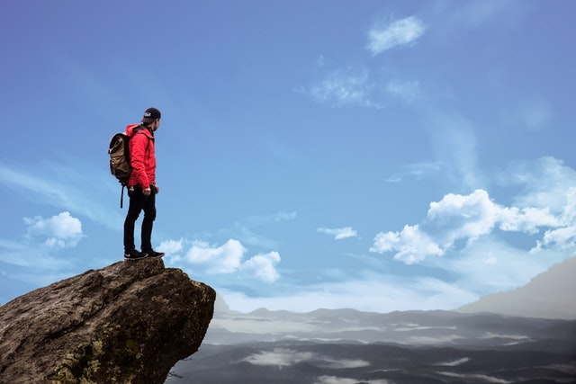 We are asked to step out in faith, just like this hiker on a cliff.