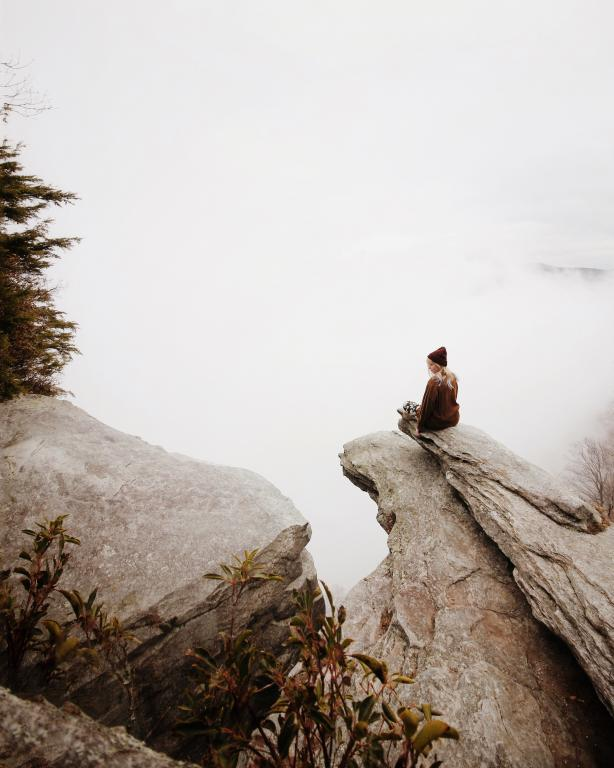 Woman sitting on a large rock reminds us that God is an everlasting and eternal rock.