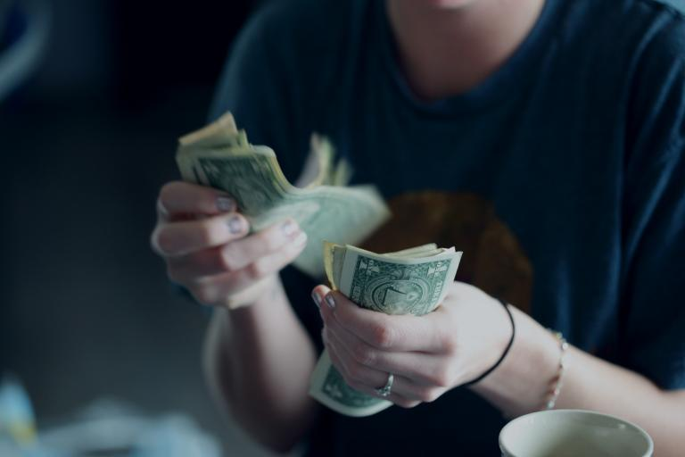 a woman counting money. Which is more important to you - God or money?