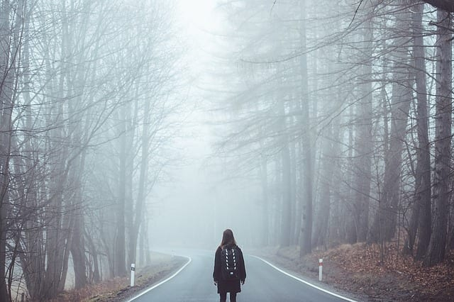 girl walking on a foggy road. Reminds us to walk by faith.