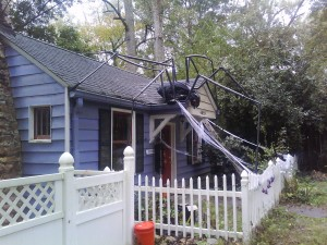 A giant spider made from PVC and a trash bag on the roof of a mild-mannered blue house with a picket fence