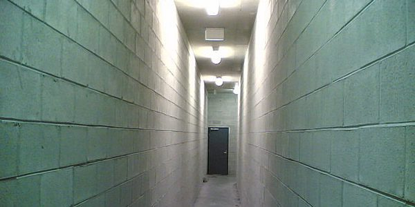 An empty hallway with a closed door at the end.