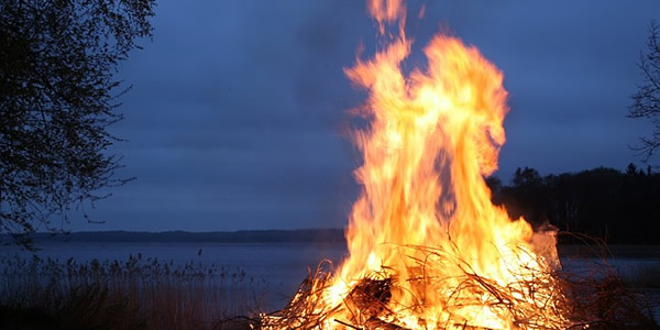 A bonfire at night near a lake
