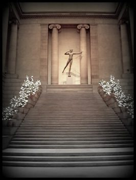 stairs rising to a statue of a female firing a bow