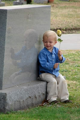 a young boy in a blue shirt sitting by a gravestone