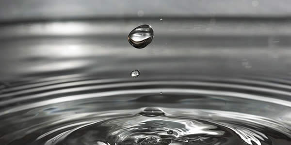a drop of water falling into a larger amount of water