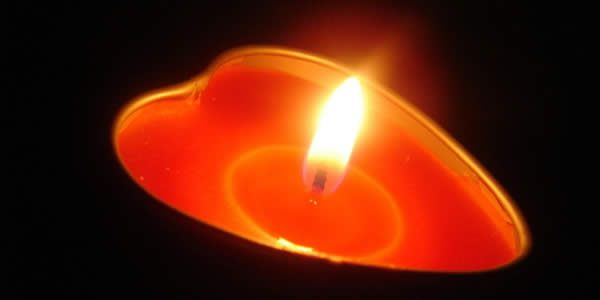 a heart shaped lit candle