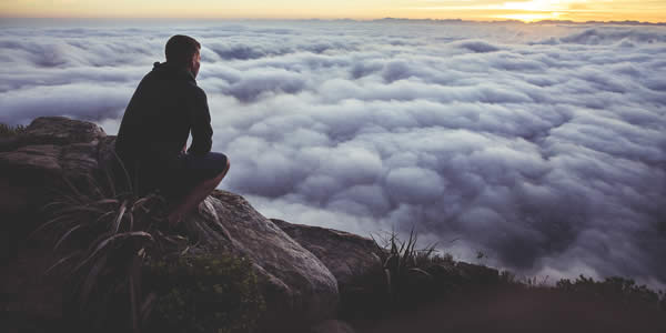 a man squatting on his heels overlooking clouds