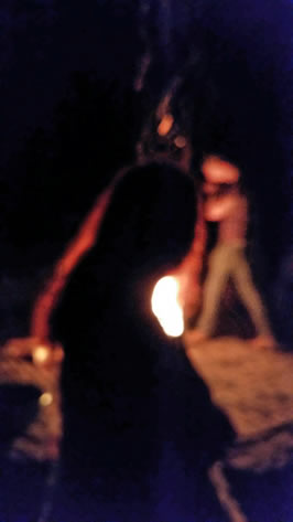 A female silhouette in front of a ritual fire