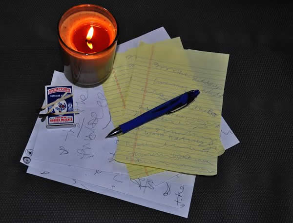 a pen, some paper, and a candle