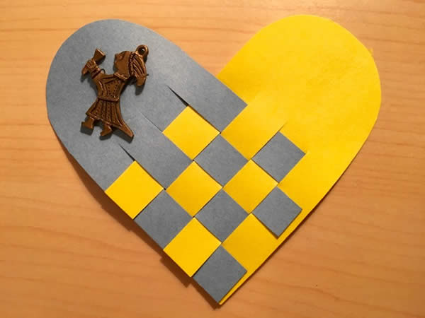 a paper heart constructed of gray and yello paper with a female figurine