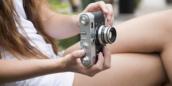 a young, white woman holding a camera