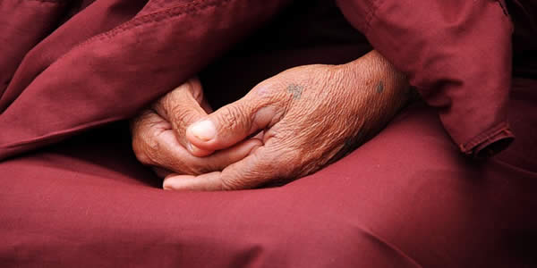 a close up of an old man's hands resting in his lap as he wears a robe